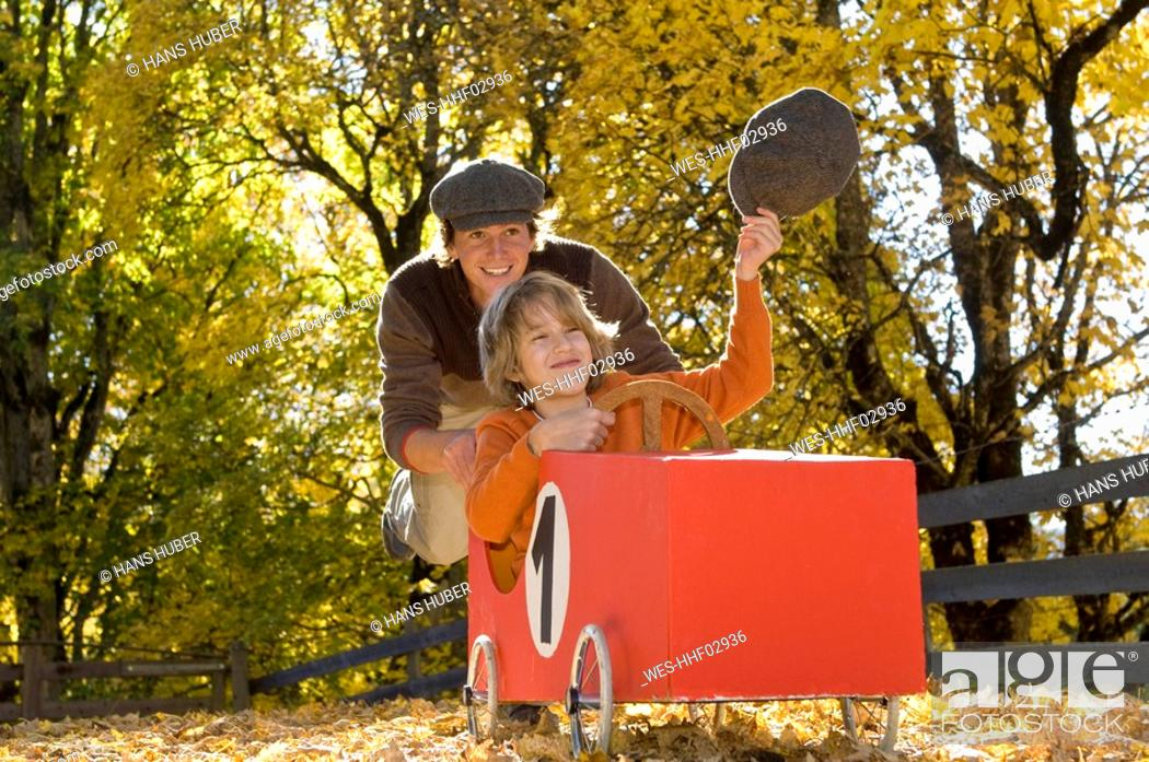 Stock Photo: Austria, Salzburger Land, Man pushing soapbox car, boy 12-13 waving cap.