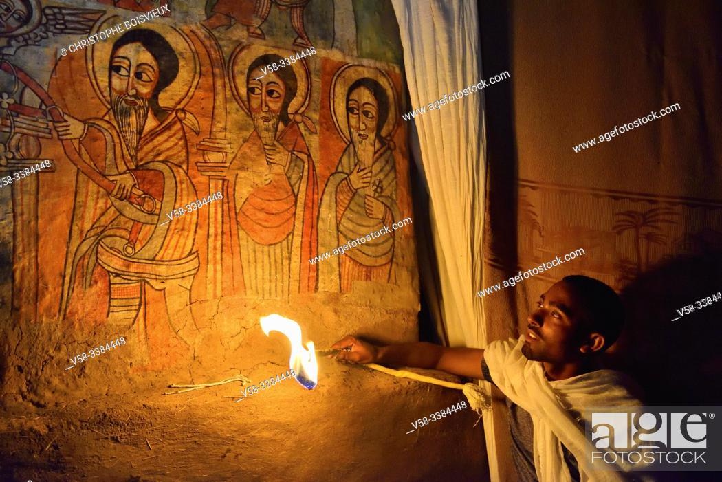 Stock Photo: Ethiopia, Lake Tana, Gorgora, Church of Debre Sina Maryam, Deacon lighting 17th C paintings representing St Anthony, St Macarius and St Bula.