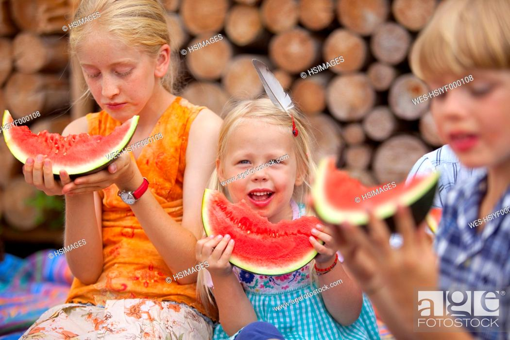 Stock Photo: Germany, Bavaria, Group of children eating watermelon.