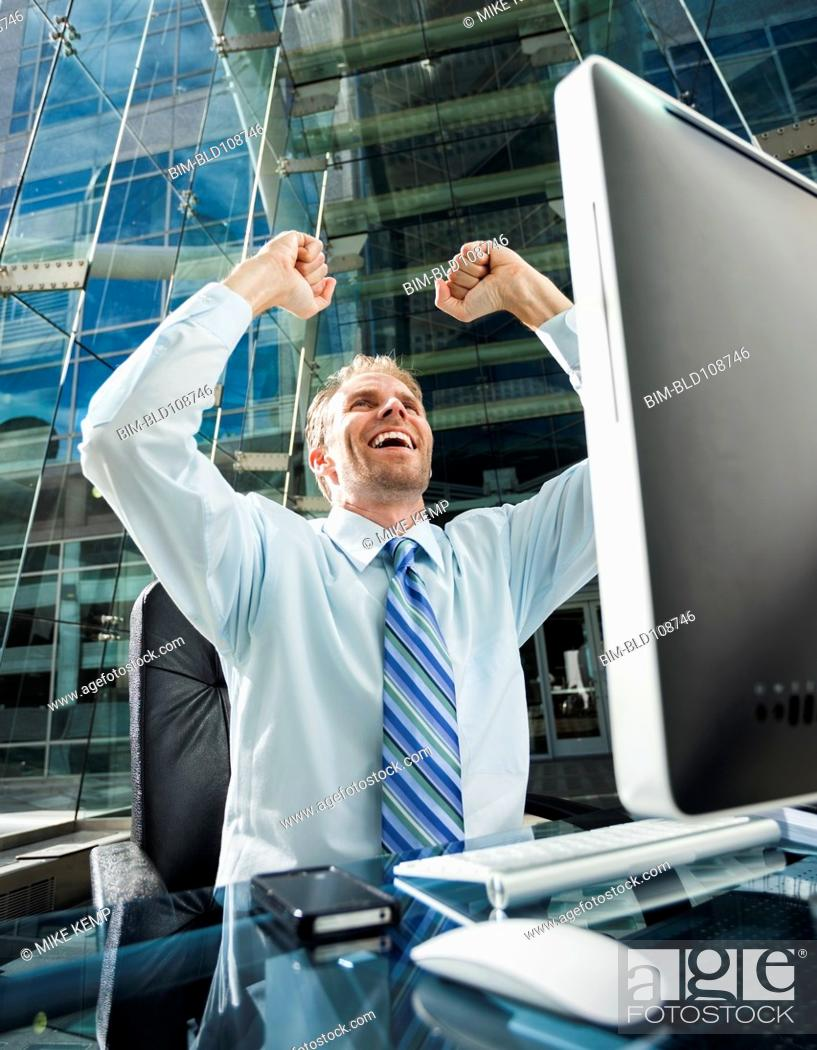 Stock Photo: Caucasian businessman cheering at computer.