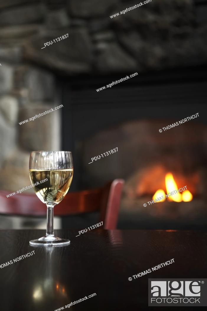 Stock Photo: Glass of white wine on table, fireplace in background focus on wine.
