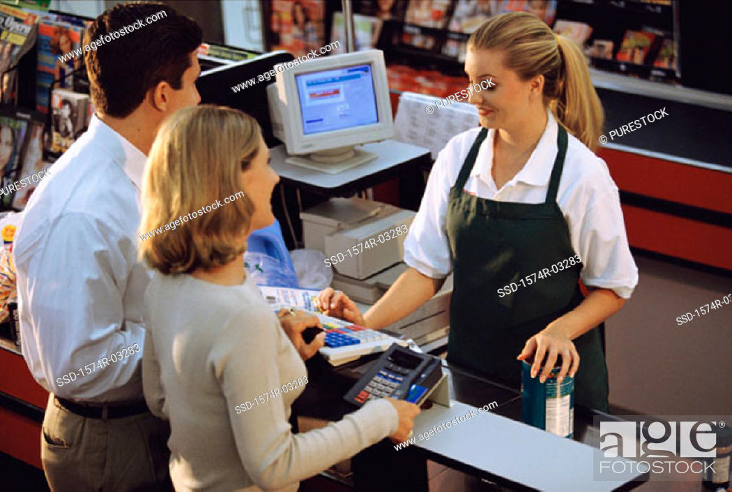 Stock Photo: Young couple standing at the checkout counter in a supermarket.