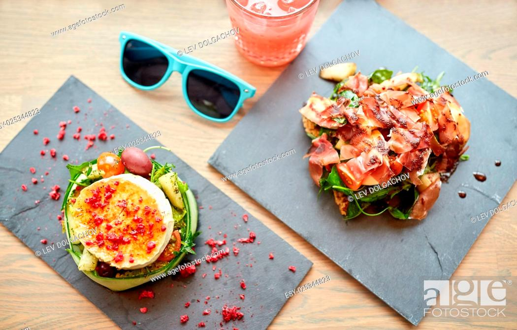 Stock Photo: food, culinary, haute cuisine and cooking concept - goat cheese and prosciutto ham salads on stone plates with glass of juice and sunglasses on table at.