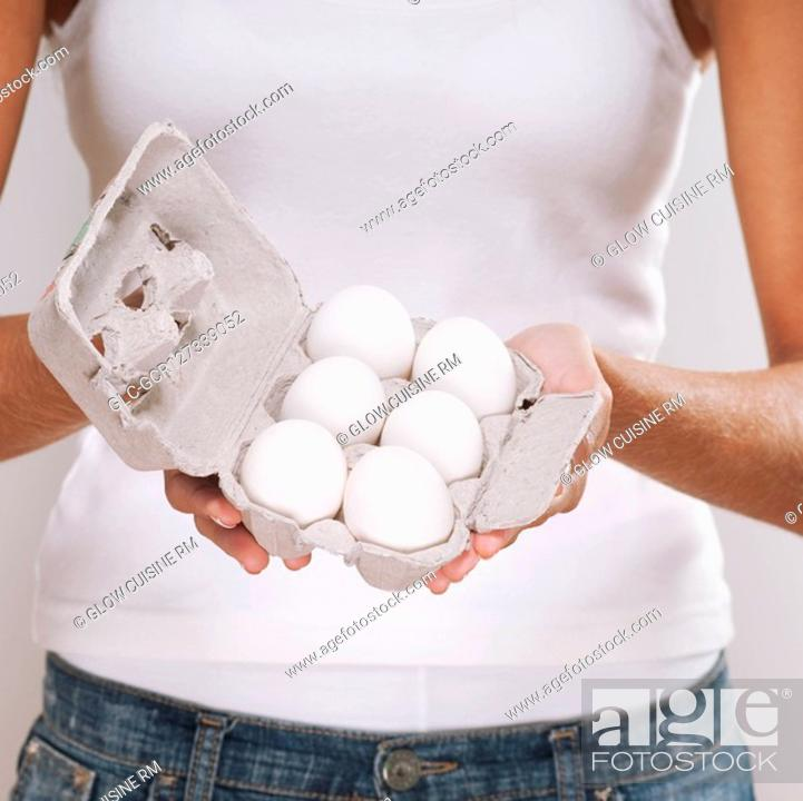 Imagen: Mid section view of a woman holding a carton of eggs.