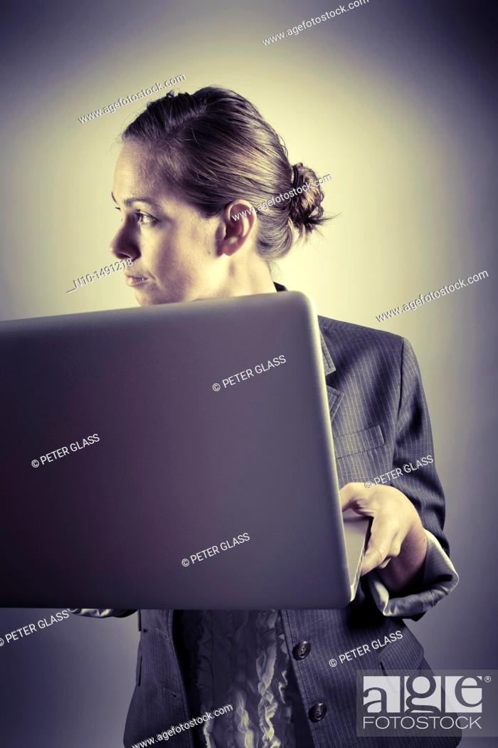 Stock Photo: Young woman working on her laptop computer.