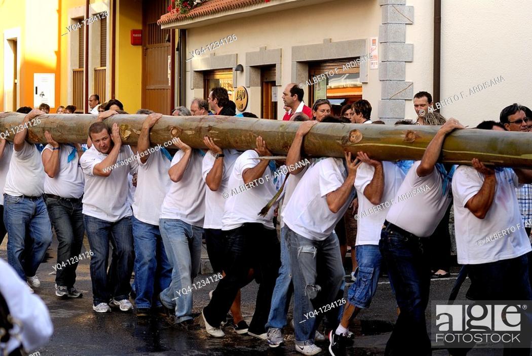 Stock Photo: Fiesta de la Blanca Village men shoulder the bonfire to plant in the town plaza Nueva de Llanes Asturias.
