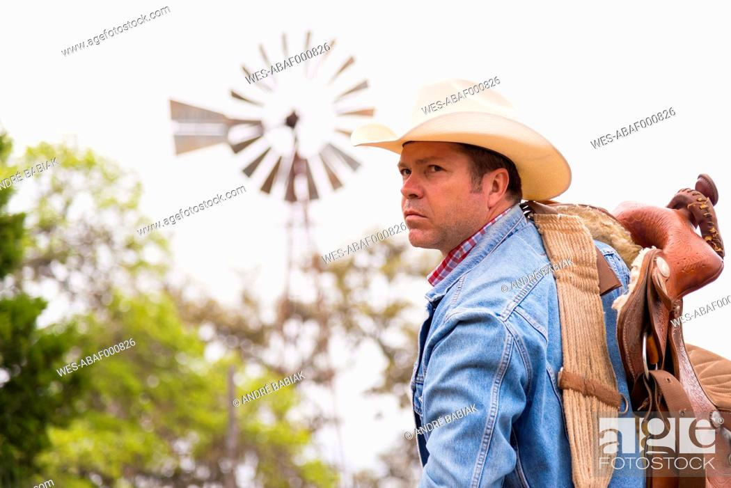 Stock Photo: Texas, Cowboy with saddle and ranch windmill in background.