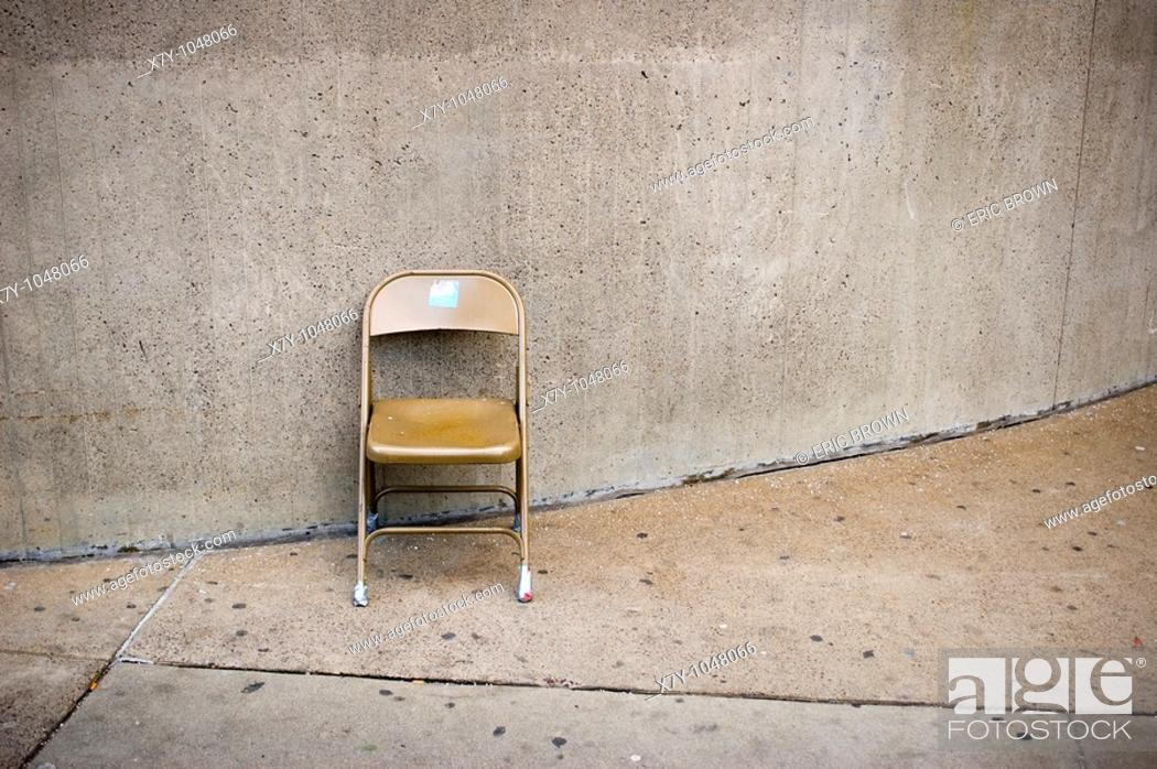 Stock Photo: A folding chair sits against a wall.
