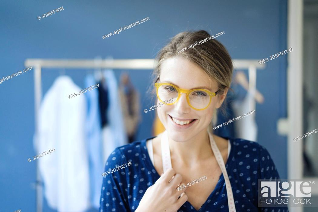 Stock Photo: Portrait of smiling fashion designer in her studio.