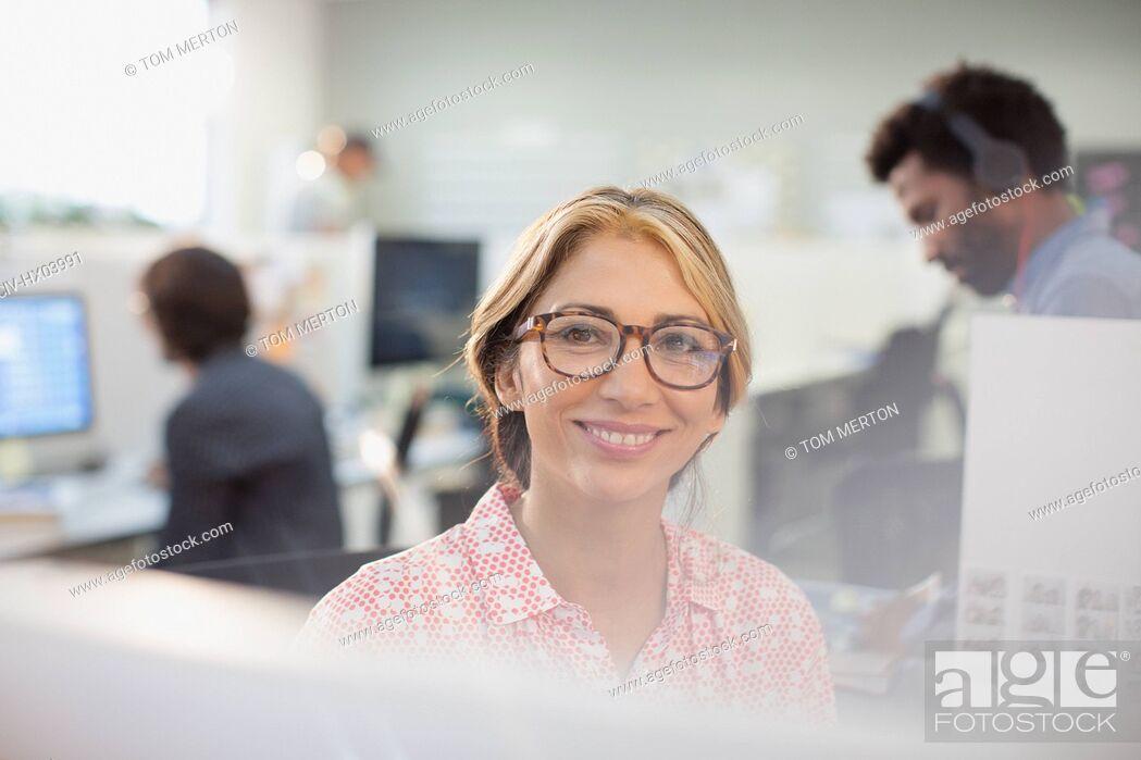 Stock Photo: Portrait smiling, confident businesswoman in eyeglasses.