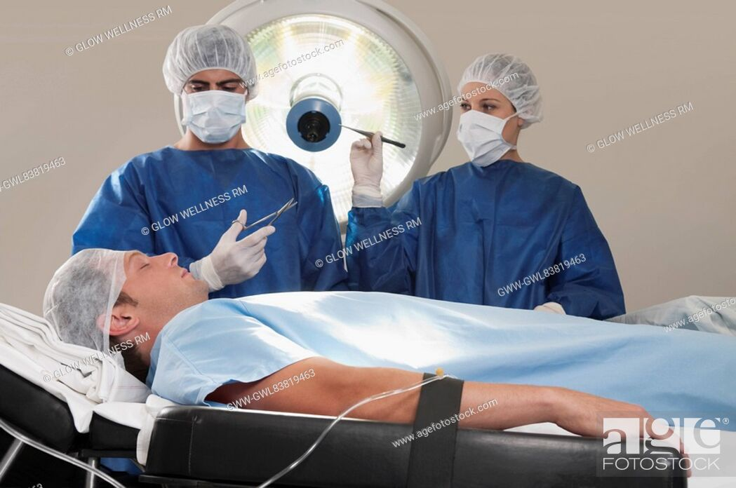 Photo de stock: Two surgeons operating a patient in an operating room.