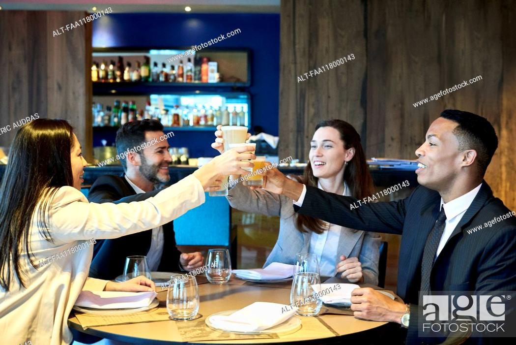 Stock Photo: Business people toasting drink in bar.