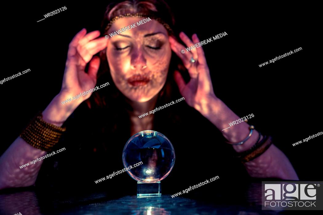 Fortune teller woman using crystal ball with eyes closed, Stock