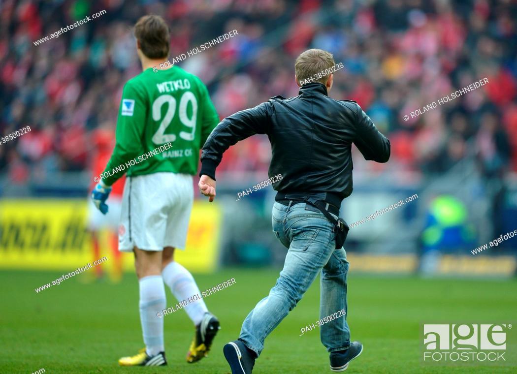 Bremen's fan runs on the pitch next to Mainz's keeper Christian ...