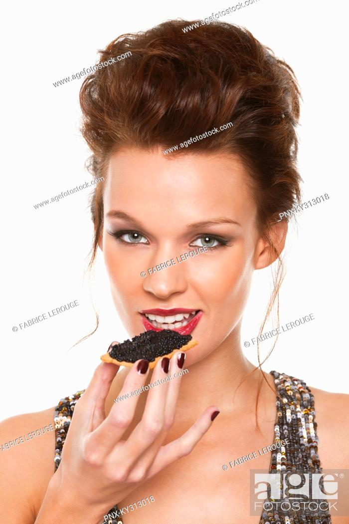 Stock Photo: Young woman eating caviar.