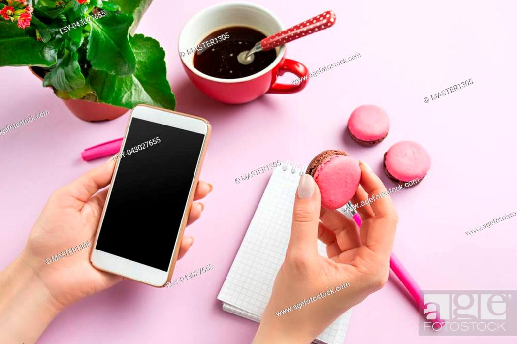 Stock Photo: Female hands holding phone. Top view on french macarons on trendy color pink desk. Woman and stilish workplace. Cup of coffee, phone, notebook.
