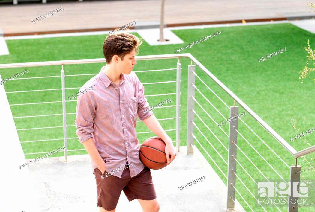 Stock Photo: Young man outdoors, holding basketball.