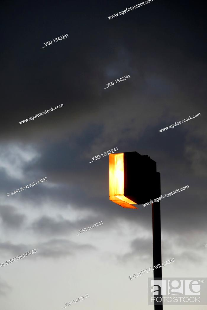 Stock Photo: one lit light bulb outdoors in dark grey sky.