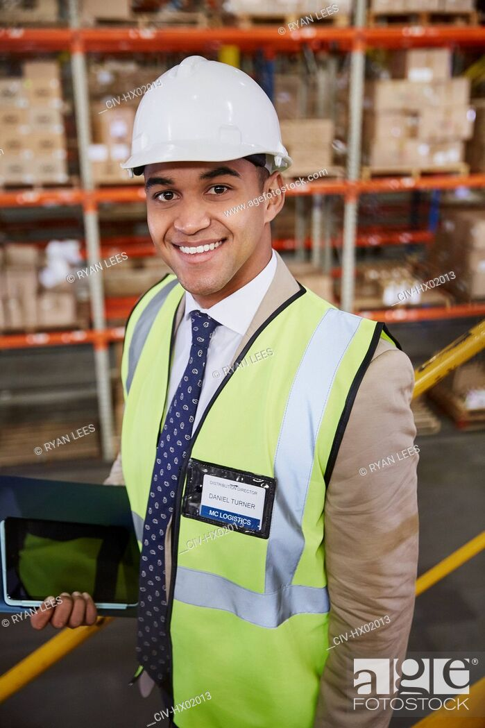 Stock Photo: Portrait smiling manager with digital tablet in distribution warehouse.