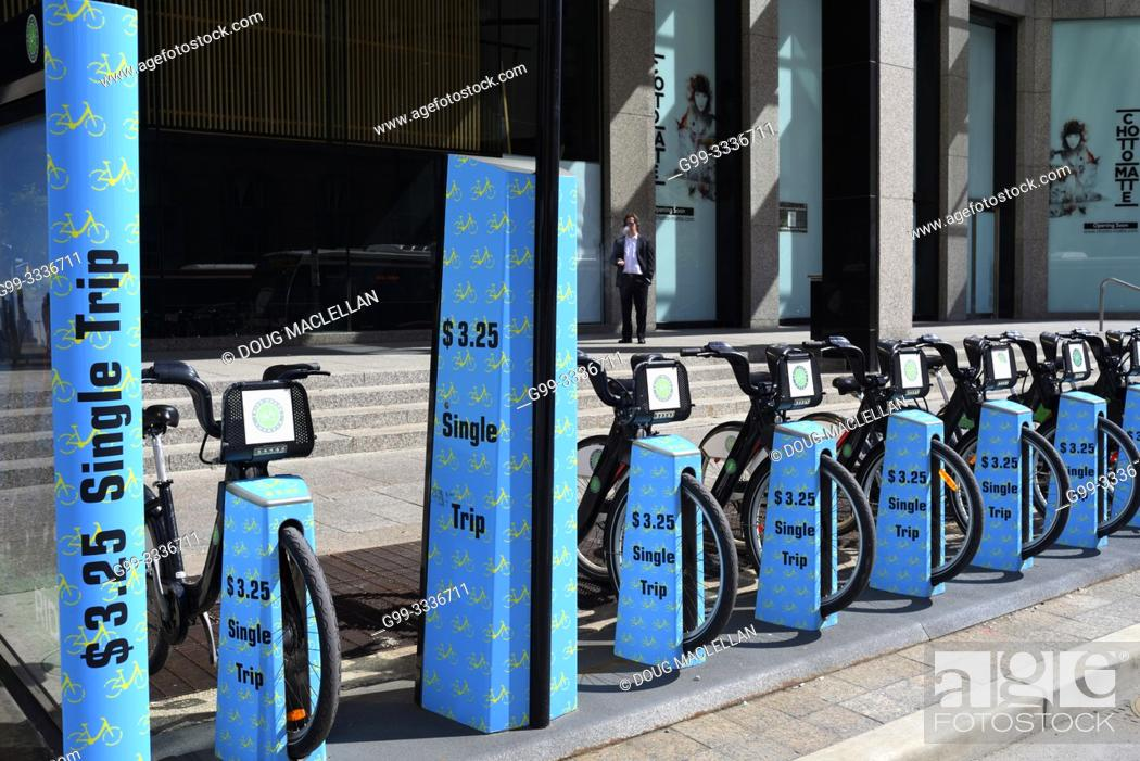 Stock Photo: A man smokes a cigarette behind a blue coloured bicycle rental spot in downtown Toronto, Ontario, Canada.