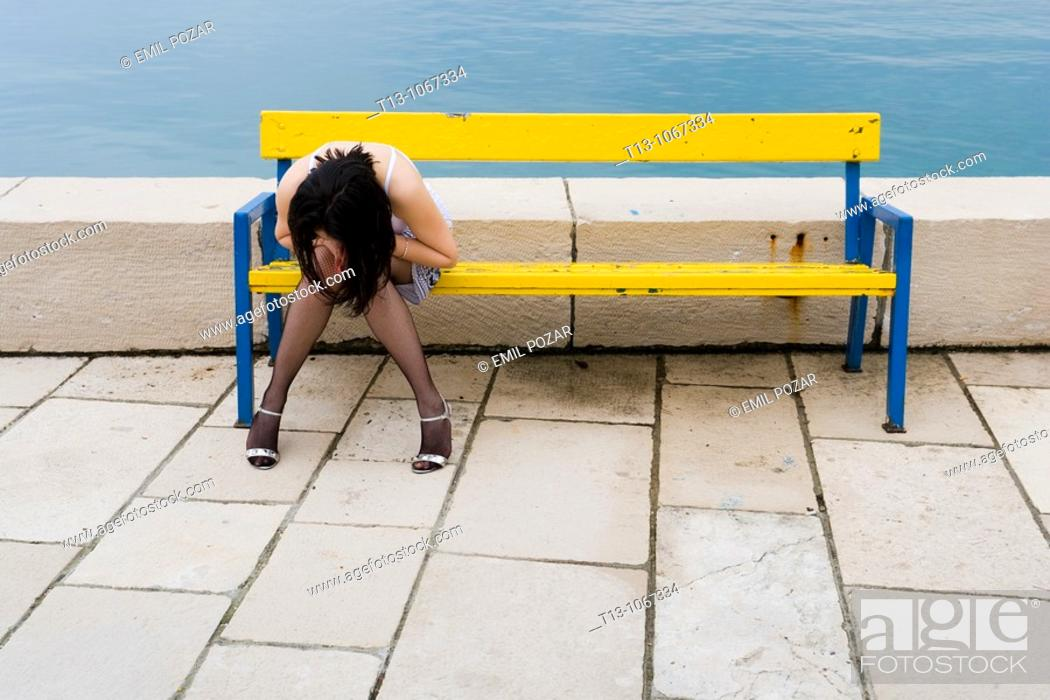 Stock Photo: Looking down pretty woman on a Yellow bench.