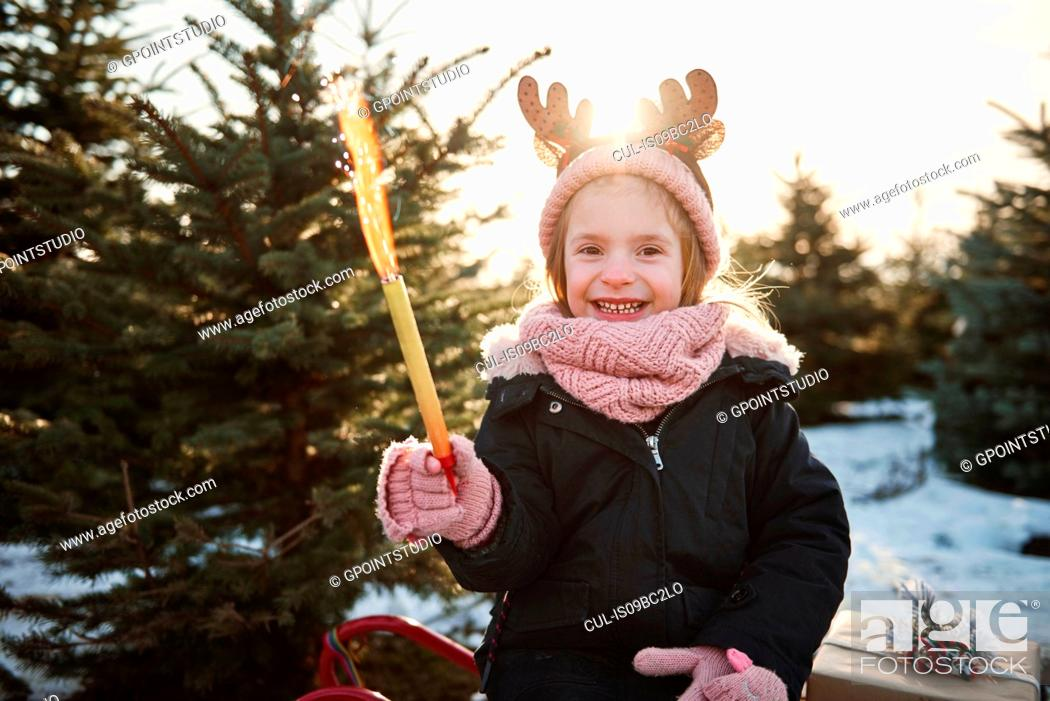 Stock Photo: Girl in christmas tree forest wearing antlers, portrait.