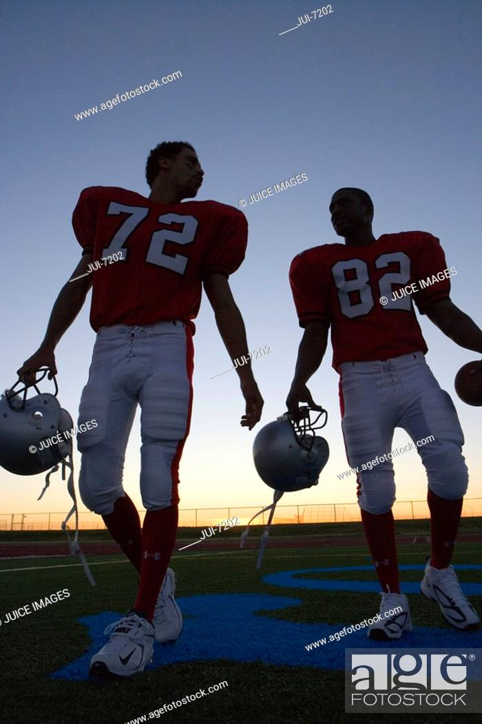 Stock Photo: Two American football players leaving pitch at sunset, side by side, front view surface level, backlit.