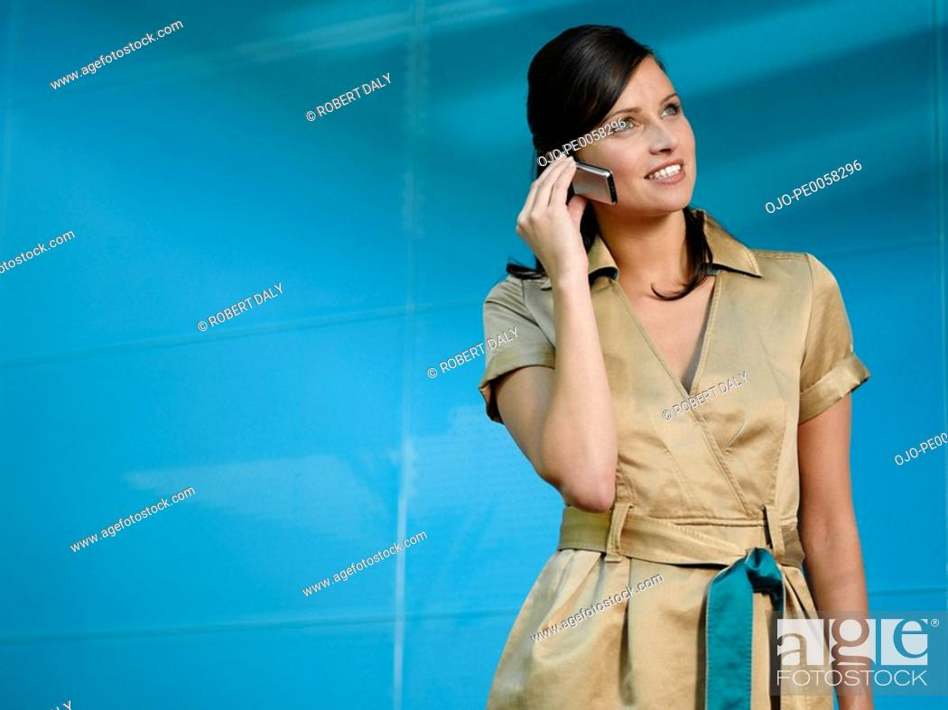 Stock Photo: Businesswoman on mobile phone in blue office.