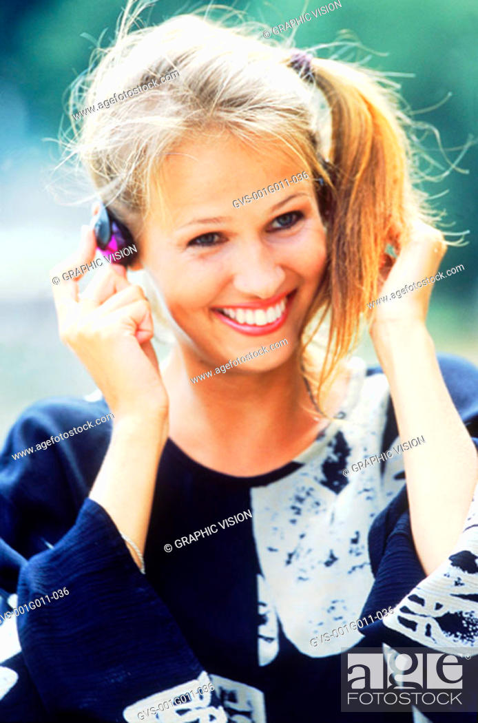 Stock Photo: Young woman wearing headphones and smiling.