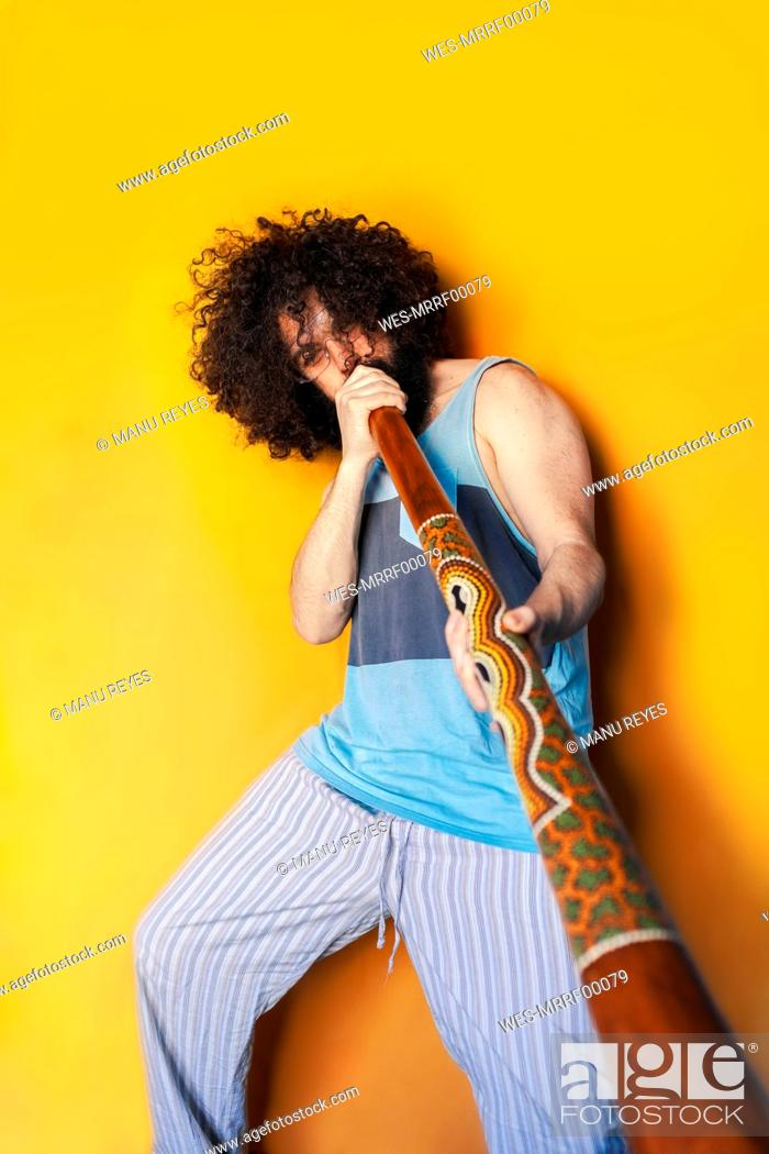 Imagen: Crazy mature man with curly hair playing didgeridoo while standing against yellow background.