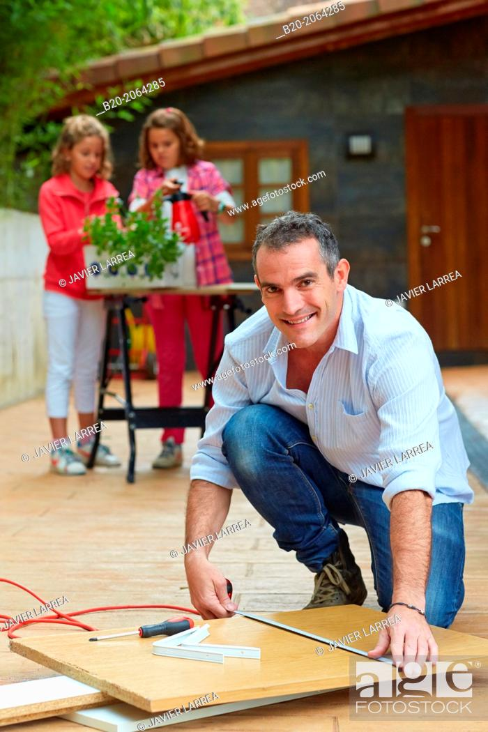 Stock Photo: Measuring a wooden board. Tinkering. Father and children doing DIY.