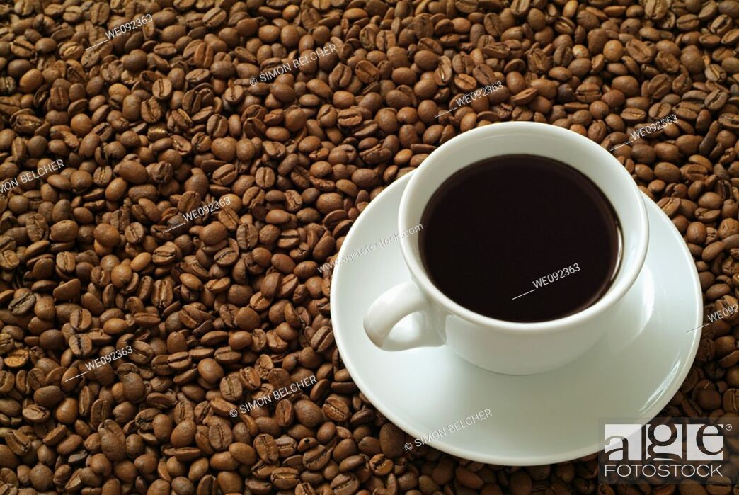 Stock Photo: Cup of Black Coffee on Coffee Beans.