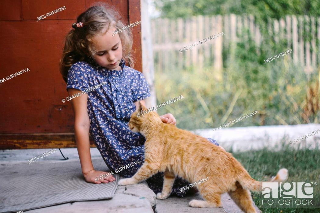 Imagen: Girl sitting on steps outdoors stroking tabby cat.