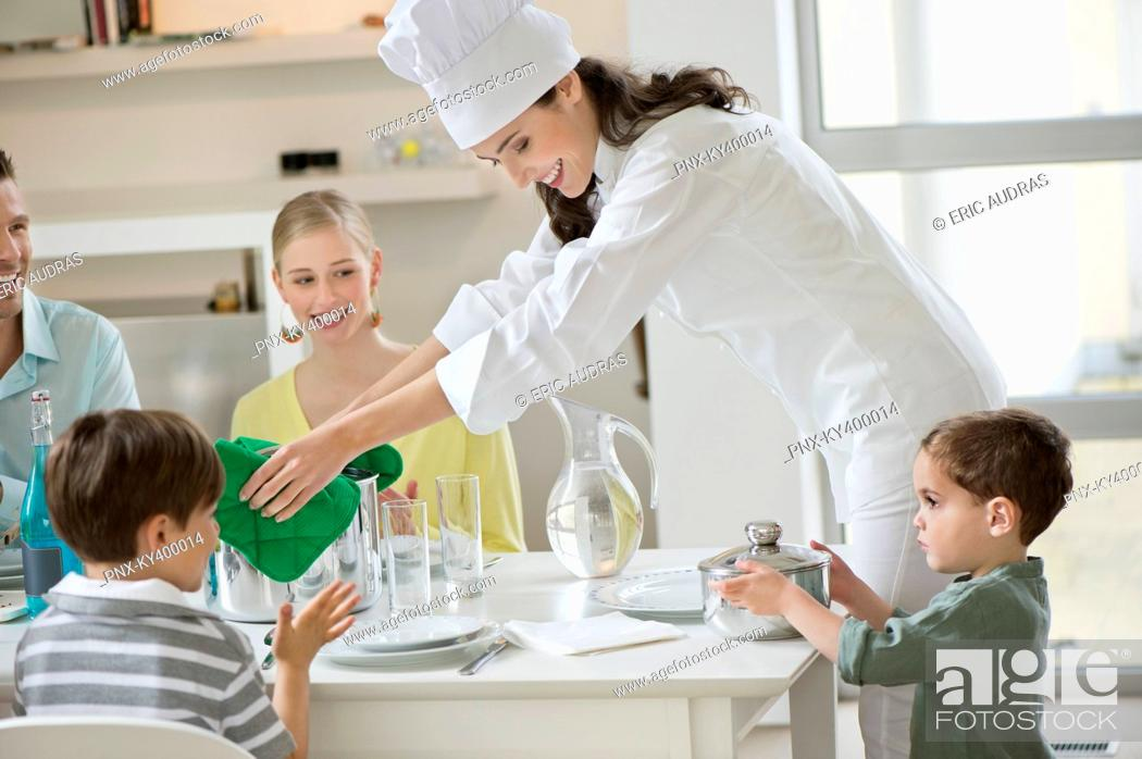 Stock Photo: Little boy assisting his mother in serving dinner.