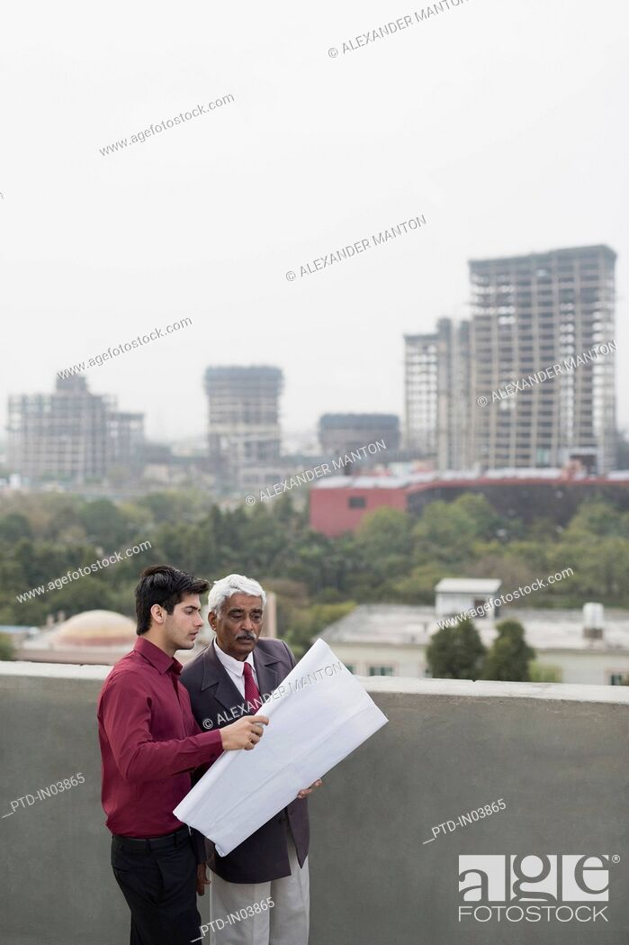 Stock Photo: India, Architects and client discussing building plans.