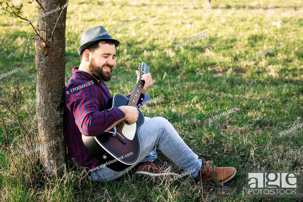 Imagen: Man playing guitar at a tree on a meadow.