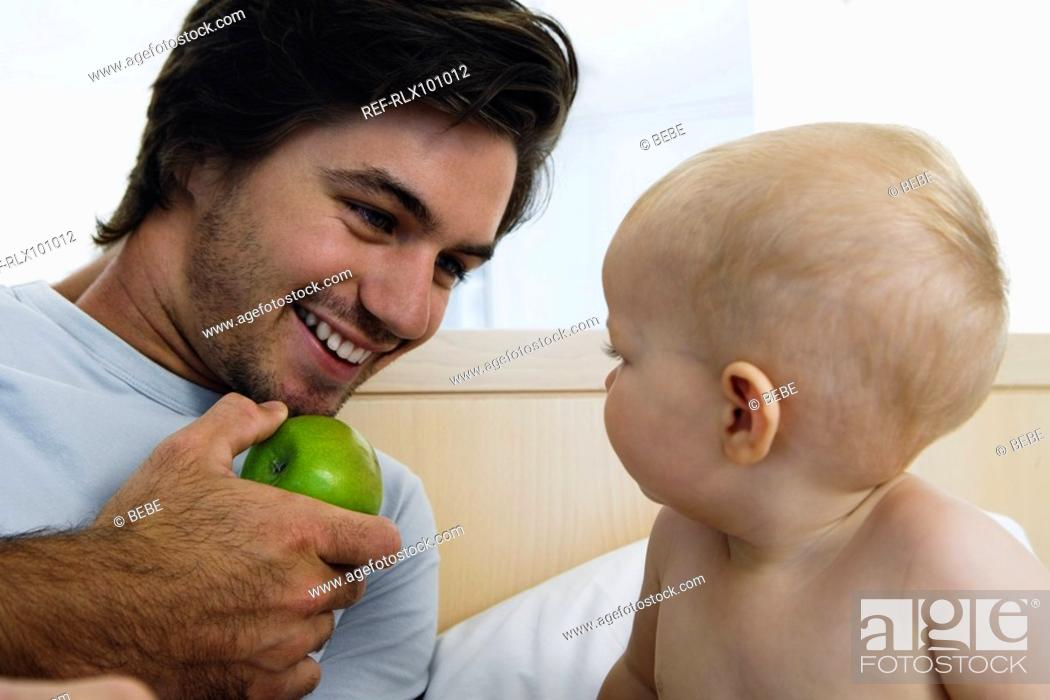 Stock Photo: Young father playing with baby 6-12 months in bed, holding green apple.