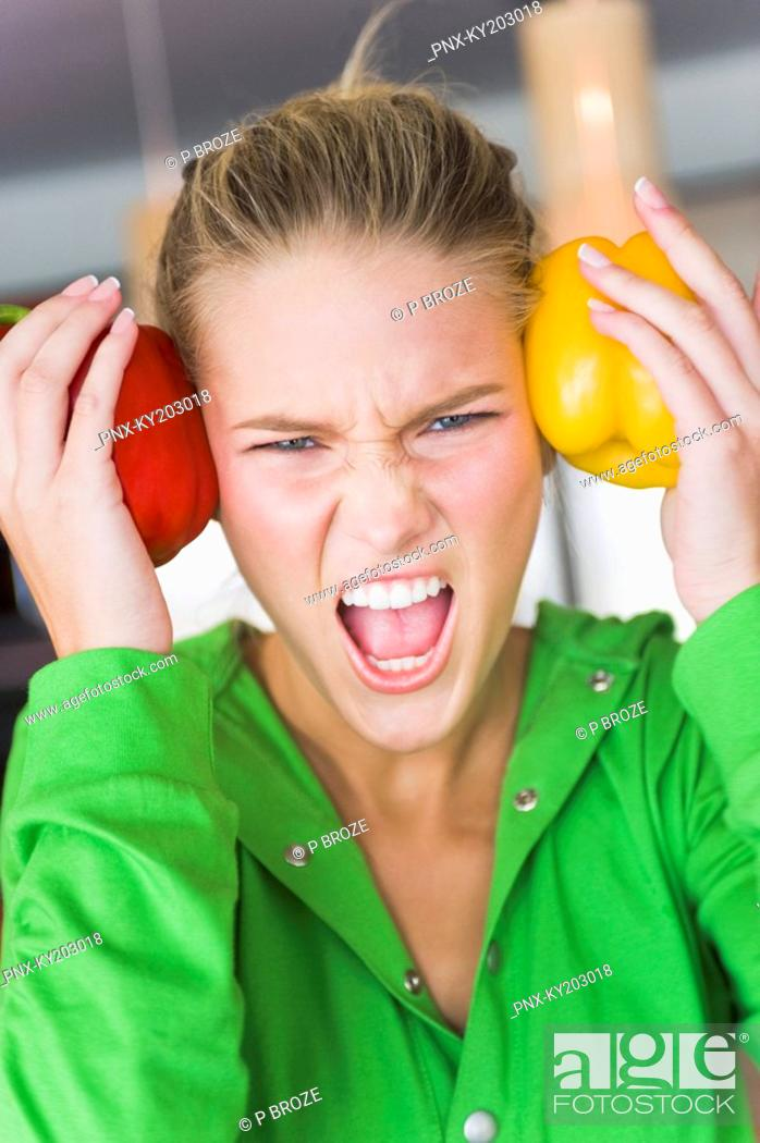 Stock Photo: Woman holding bell peppers on her temples and shouting.
