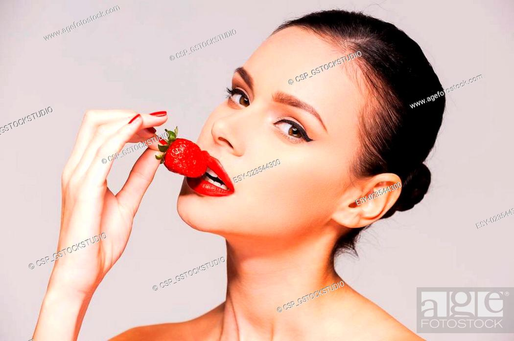 Stock Photo: Let me tempt you! Beautiful young shirtless woman holding strawberry in her hand while standing against grey background.