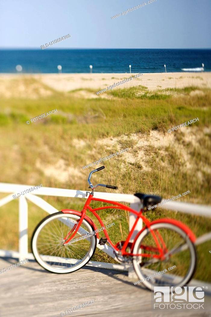 Stock Photo: Red beach cruiser bicycle leaning against walkway rail on beach on Bald Head Island, North Carolina.
