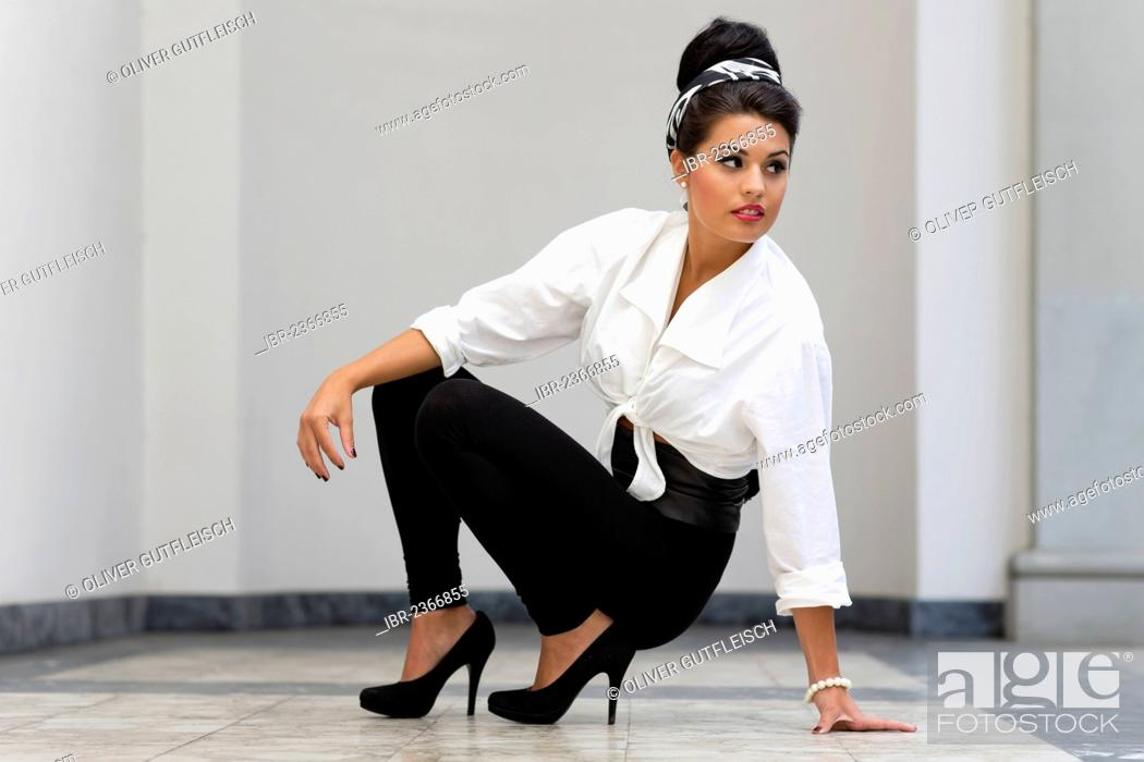 2556edf42 Stock Photo - Young woman with an updo hairstyle wearing a white blouse,  black leggings and high heels, fashion