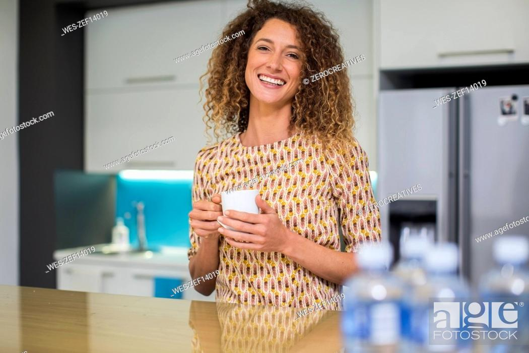 Stock Photo: Portrait of smiling woman in office kitchen holding cup.