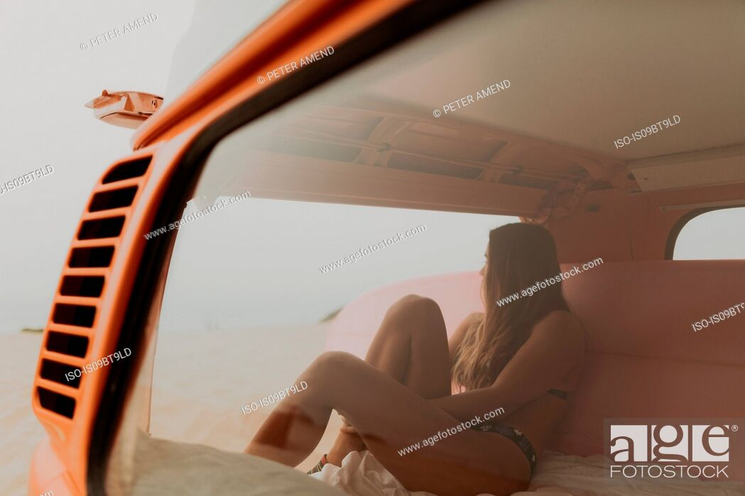 Stock Photo: Young female surfer looking out from recreational vehicle at beach, Jalama, California, USA.