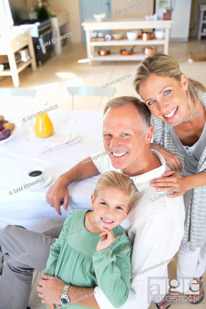 Stock Photo: Portrait of smiling parents with daughter at breakfast table.