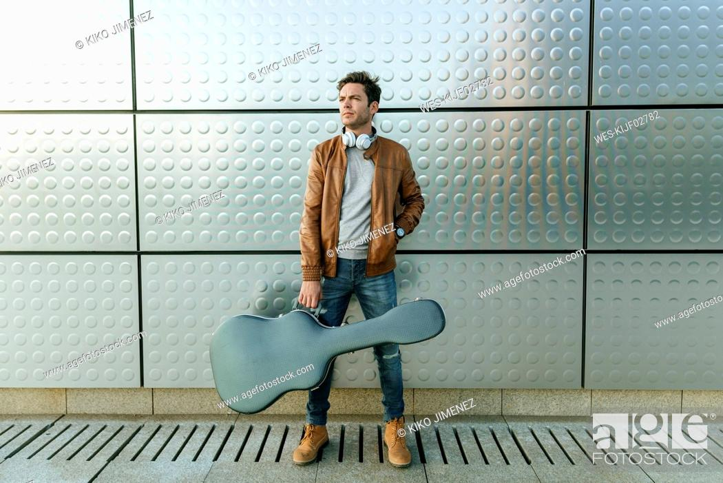 Imagen: Man with guitar standing in front of a silver wall.