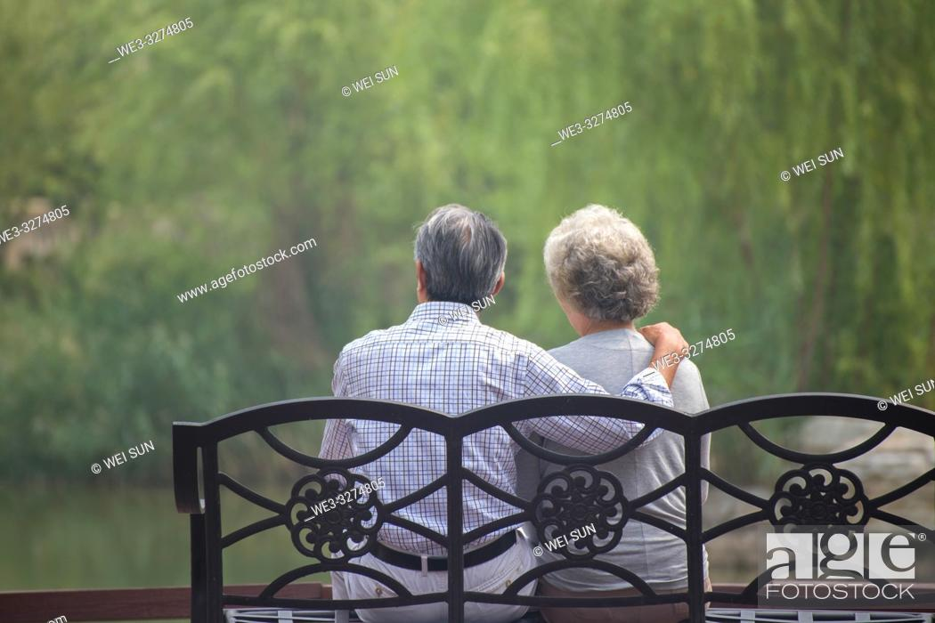 Imagen: Elderly couple outdoors, sitting on bench.