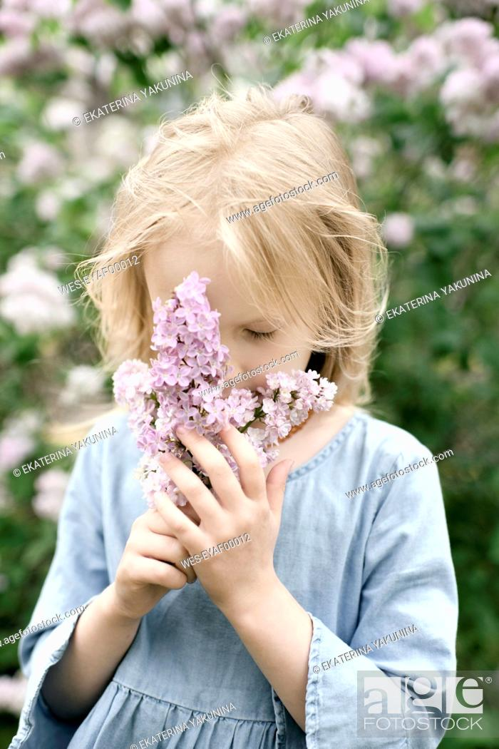 Stock Photo: Portrait of smiling girl with lilac blossoms, sniffing.