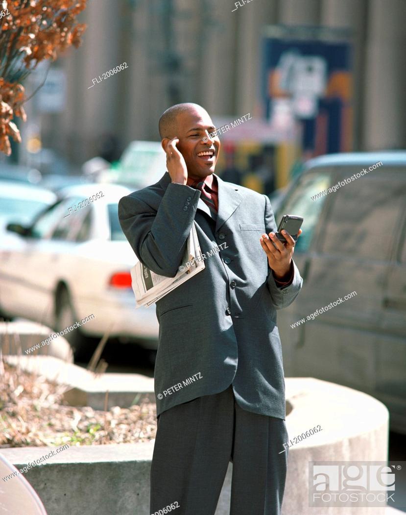 Stock Photo: Fl6190, Peter Mintz; Businessman Holding Blackberry And Newspaper.