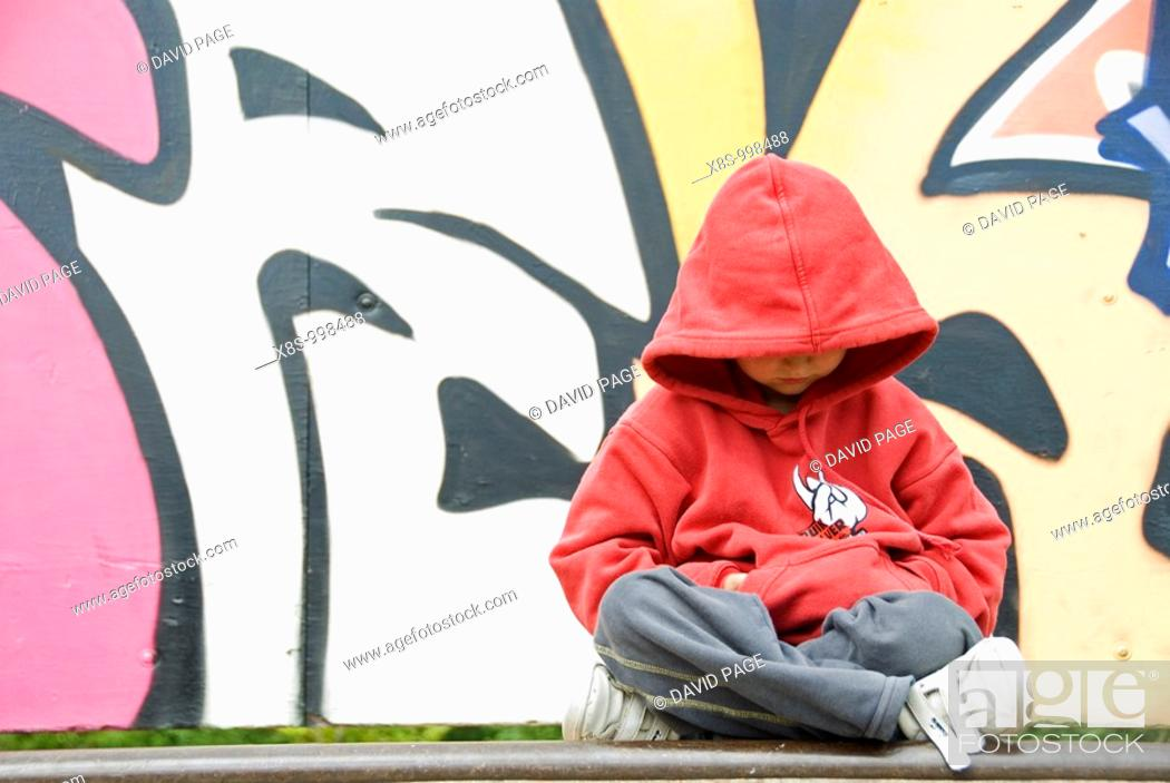Stock Photo: Stock photo of a young boy sitting cross legged in front of a wall covered with Graffiti.