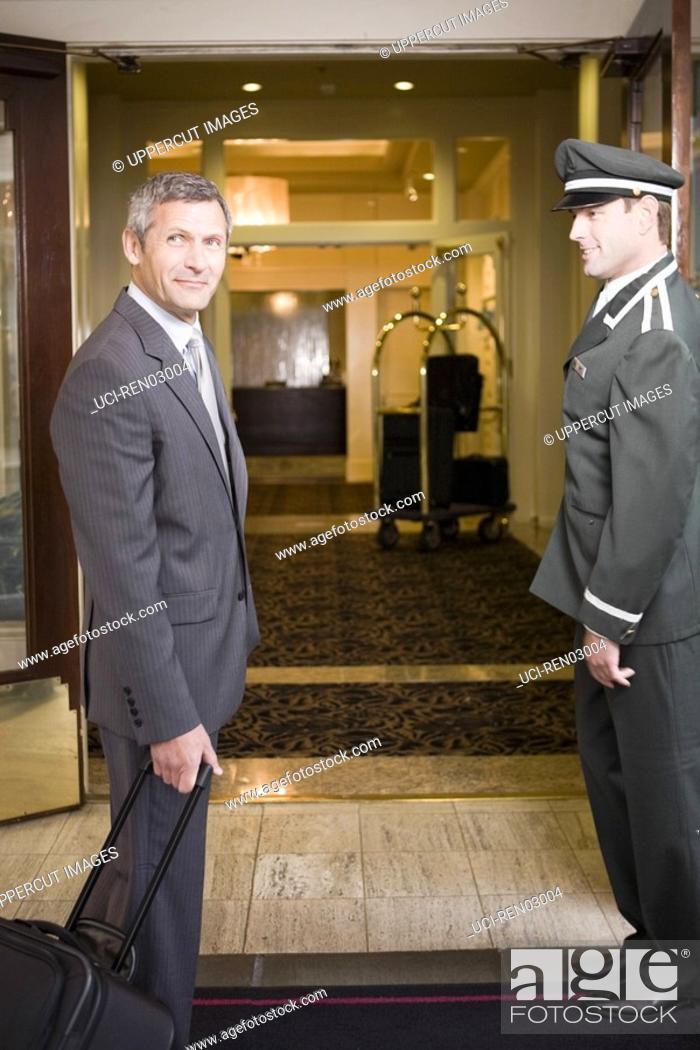 Stock Photo: Businessman and bellhop in hotel doorway.